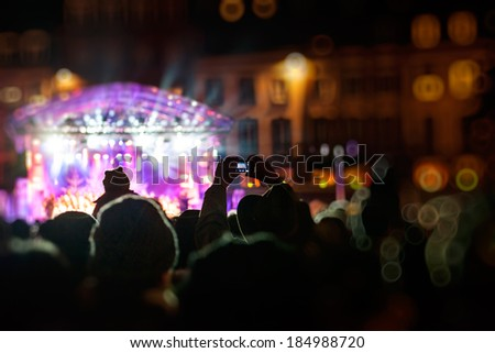 Man photographing with smartphone during a public concert or celebration a funny stage with multiple lights - stock photo