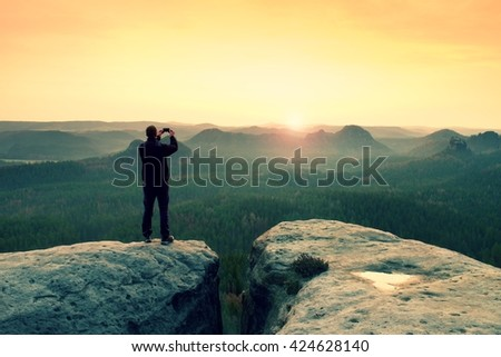 Man photography with phone of  dreamy hilly landscape, spring orange pink misty sunrise in a beautiful valley of rocky mountains.