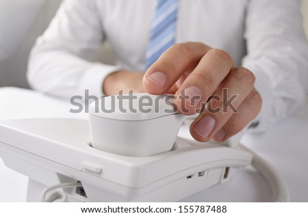 Man picking up a telephone handset on a land line telephone, close up view of the instrument and his hand - stock photo