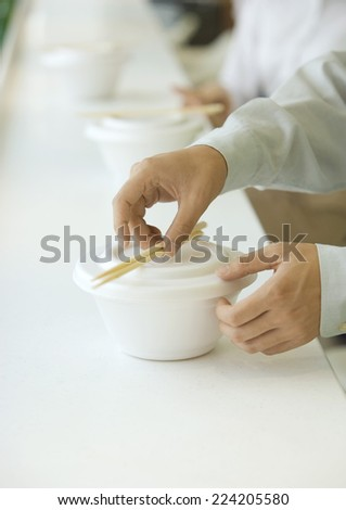Man picking up chopsticks on take-out food container, cropped view - stock photo