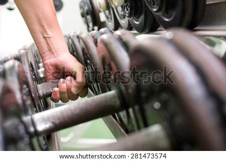 Man picking up dumbbells in a gym at the University of Las Palmas de Gran Canaria - stock photo