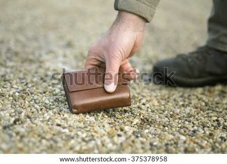 Man picking up fallen leather wallet on ground - stock photo
