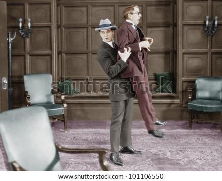 Man picking up frightened man - stock photo