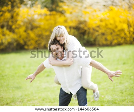 Man piggybacking woman in park