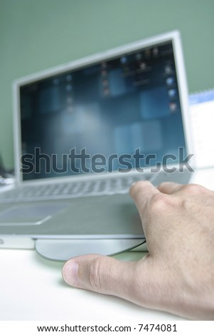 Man placing cd in laptop