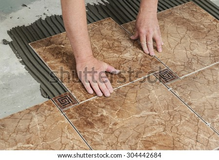 Man placing ceramic floor tile in position over adhesive - stock photo