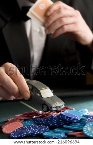 Man placing model car on pile of gambling chips on table, mid section - stock photo