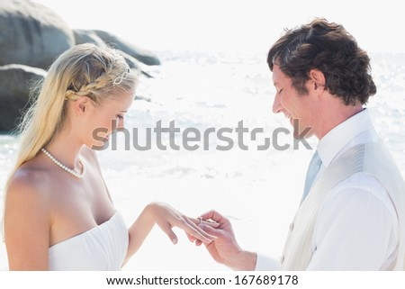 Man placing ring on happy brides finger at the beach