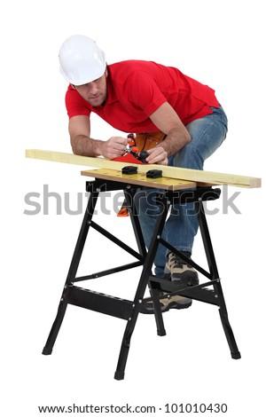 Man planning plank of wood - stock photo