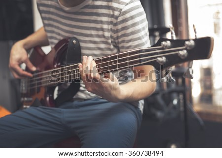 Man play on bass guitar - stock photo
