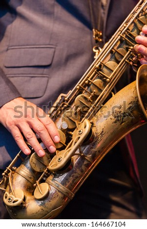 Man playing a brass tenor saxophone or sax during a live performance in an orchestra, a popular reed instrument in jazz, blues and country music - stock photo