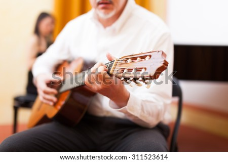 Man playing a classical guitar in a concert hall - stock photo