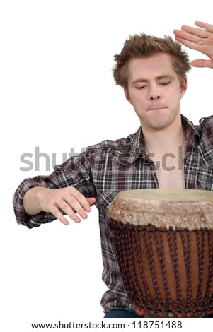 Man playing a djembe drum - stock photo