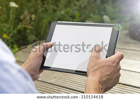 Man, playing a game on a tablet outdoors. The tablet has a white screen, for your app or website presentation - stock photo