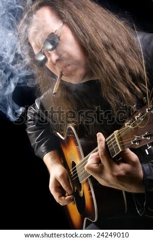 Man playing acoustic guitar and smoking cigar - stock photo