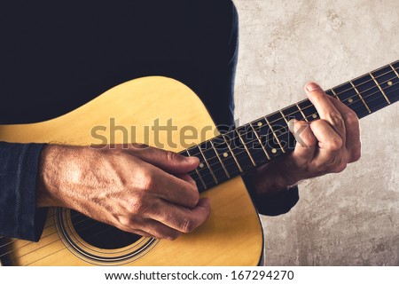 Man playing acoustic guitar, unplugged performance. - stock photo