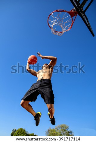 Man playing basketball outdoors - stock photo