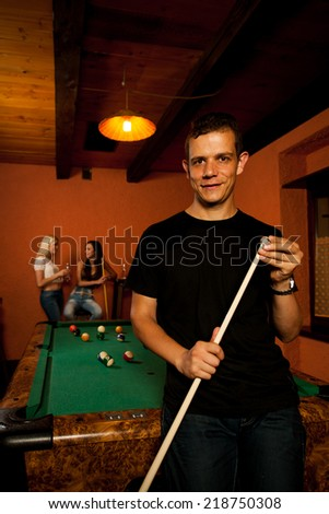 Man playing billiard in a bar at night - stock photo