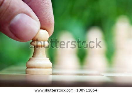 man playing chess and hold pawn - stock photo