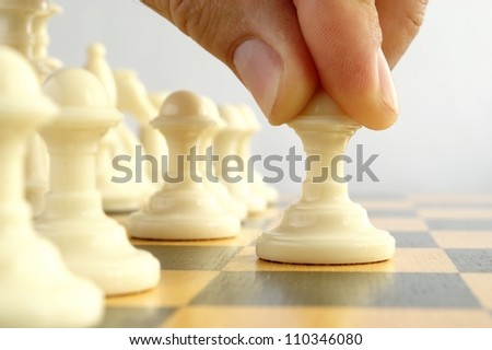 man playing chess, and shows the hand of chess pieces - stock photo