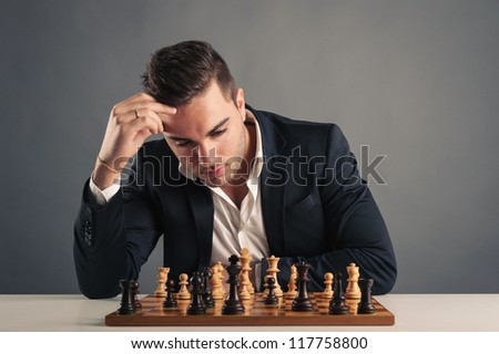 Man playing chess, isolated on dark background. - stock photo