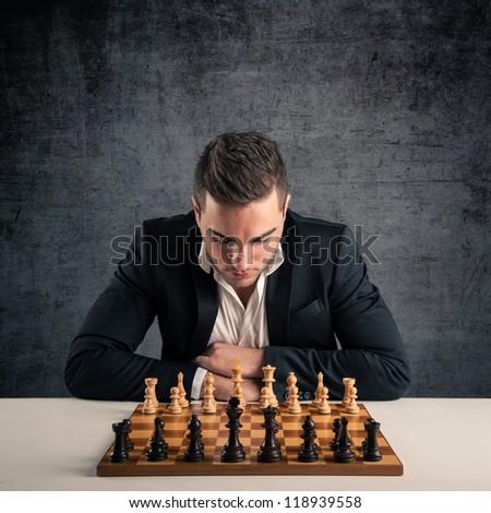 Man playing chess, isolated on dark grunge background. - stock photo
