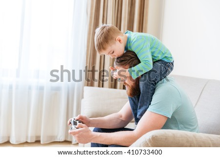 Man playing computer games while his little son covering his eyes sitting on sofa at home - stock photo