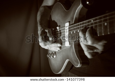 Man playing electric guitar at black background