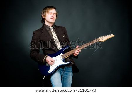 Man playing electro guitar, studio shot - stock photo
