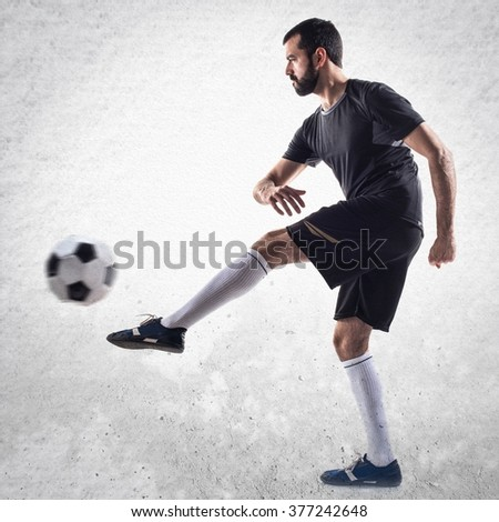 Man playing football over textured background - stock photo