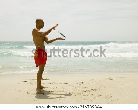 Man playing frisbee on the beach. - stock photo