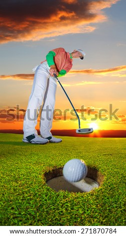 Man playing golf against colorful sunset - stock photo