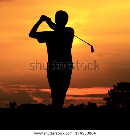Man playing golf against sunset background - stock photo