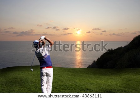 man playing golf  against sunset over sea - stock photo