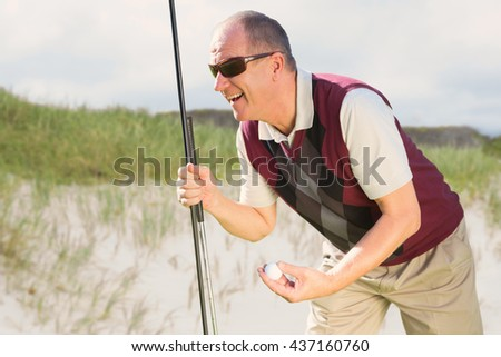 Man playing golf against view of sand - stock photo