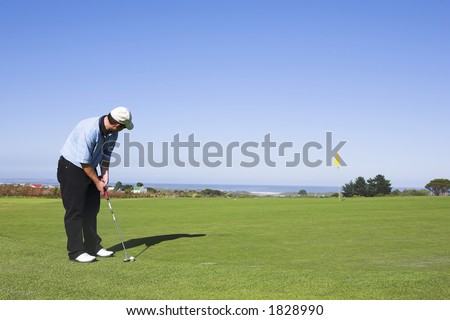 Man playing golf aiming for hole. - stock photo