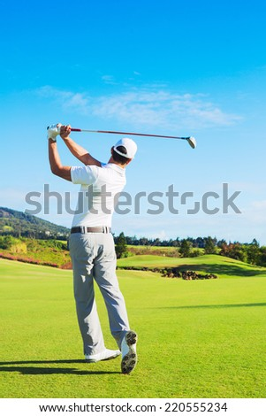 Man Playing Golf on Beautiful Sunny Green Golf Course. Hitting Golf Ball down the Fairway. - stock photo