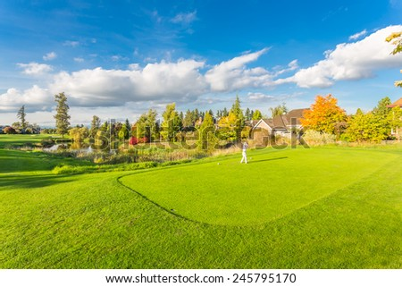Man playing golf on beautiful sunny green golf course with pond in Vancouver, Canada - stock photo