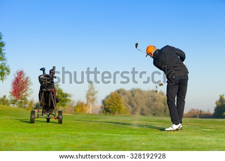 Man playing golf on green golf course. Hitting golf ball - stock photo
