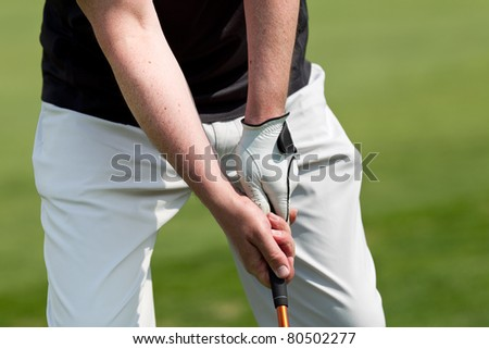 man playing golf while wearing a blue polo and white trousers