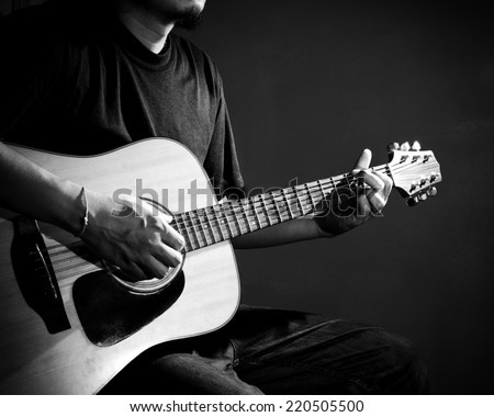 Man playing guitar. Black and white photo.