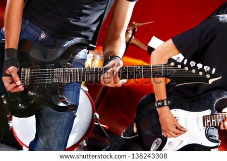 Man playing  guitar in night club. Lighting effects. - stock photo