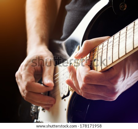 Man playing guitar on a stage. Musical concert. Close-up view. - stock photo