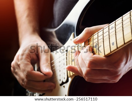 Man playing guitar on a stage. Musical concert. Close-up view. Live rock stars performing musical hits. Guitar solo in the spotlight. Musician pluck the strings with the help of a plectrum. - stock photo