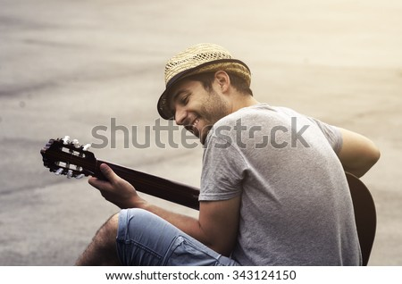 Man playing guitar on the street. retro style. - stock photo