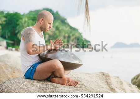 Man playing hang drum sitting on the stone at tropical beach