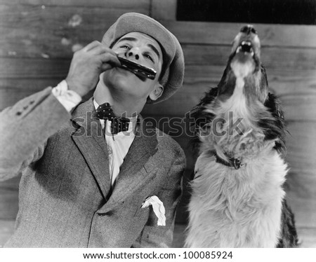Man playing harmonica with howling dog - stock photo