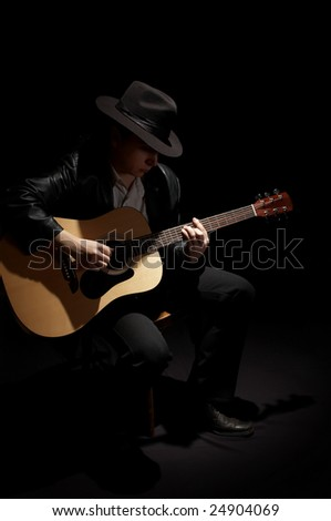 man playing his acoustic guitar - stock photo