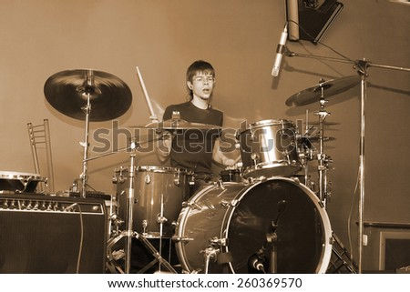 man playing on drum on grey background - stock photo