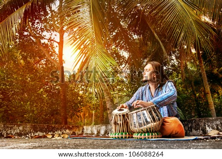 Man playing on traditional Indian tabla drums at sunset tropic background - stock photo